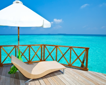 lounges: Parasol and chaise lounges on a terrace of water villa, Maldives. Stock Photo