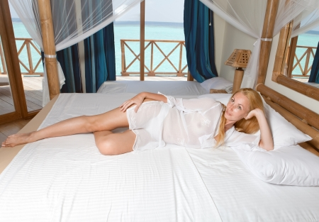 Young pretty woman in bed with ocean behind window. photo