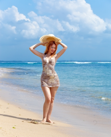 Young beautiful woman goes on ocean coast with straw hat in hands photo