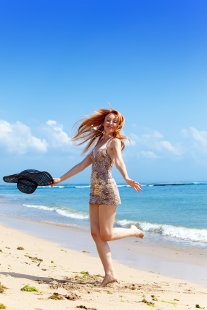 Young  woman goes on ocean coast  with hat photo