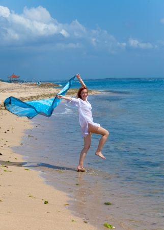 The young attractive woman jumping in the sea photo