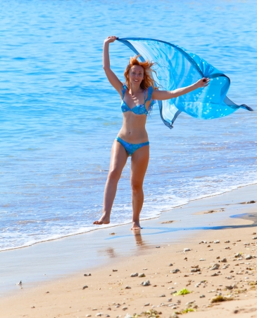 The young attractive woman on a beach with a blue scarf in hands photo