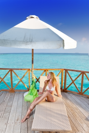 tans: Young woman tans on a water villa terrace , Maldives