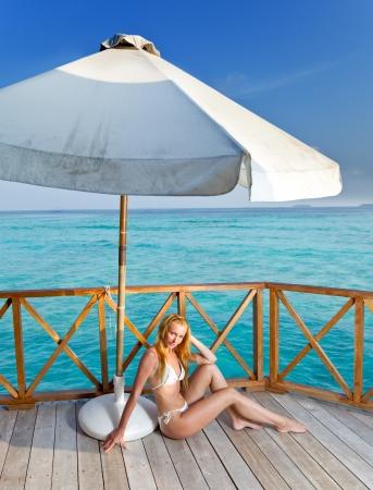 tans: Young woman tans on a water villa terrace , Maldives   Stock Photo