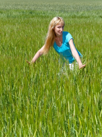 The happy young woman in the field of green ears   photo