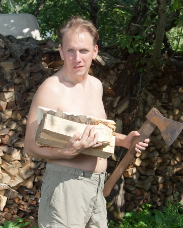 The man with a splitting axe prepares firewood to heat the house photo