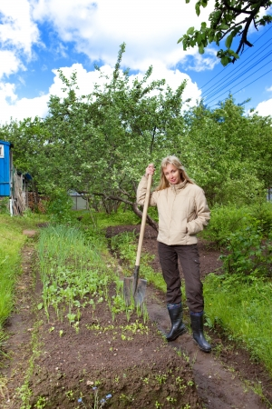 The young woman digs up a garden-bed with the first sprouts on a summer cottage photo