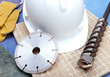 Diamond disk, drill and a helmet on a tile