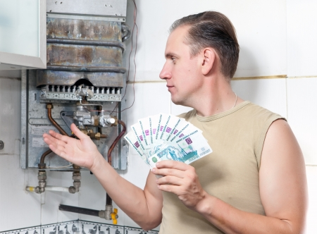 The sad man counts money for repair of a gas water heater photo
