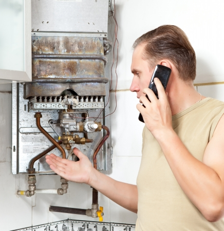 The man calls by phone to cause the repairman of gas water heaters photo
