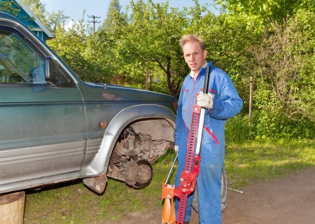 replaces: The man in working overalls replaces a wheel at an off-road car