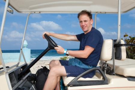 Man by golf car on the seashore. Mexico. Women Island. photo