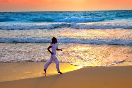 sporting woman is engaged in run on the sea coast on a beach   photo