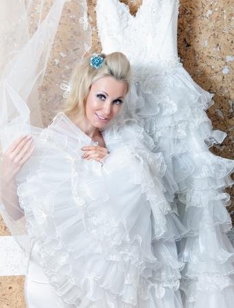 The beautiful woman tries on a wedding dress. Stock Photo