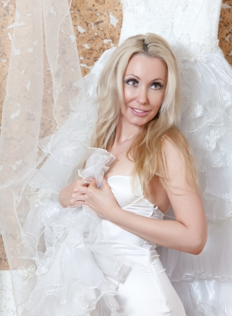 ruching: The young woman with a wedding dress in hands dreams of wedding