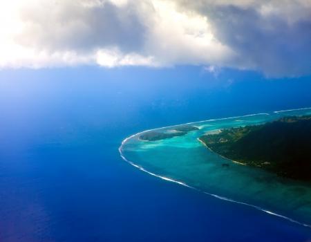 bora: Polynesia. The atoll in ocean through clouds. Aerial view