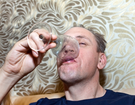 The unshaven man finishes drinking the last drink of alcohol from a glass photo