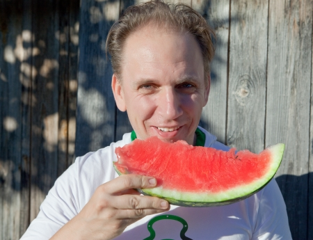 the happy man with a piece of a water-melon photo