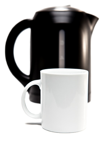 electric tea kettle on a white background and a mug  Focus on a tea mug photo
