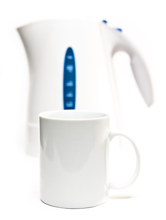 electric tea kettle: Focus on a tea mug. Electric tea kettle on a white background and a mug Stock Photo