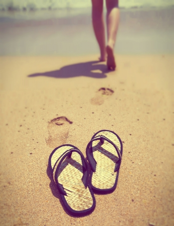 young female: slippers on sand, and female feet out of focus ,with a retro effect