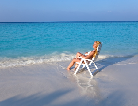 tans: Young pretty woman tans in beach chair Stock Photo