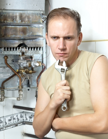 The man with a wrench thinks of repair of a gas water heater photo