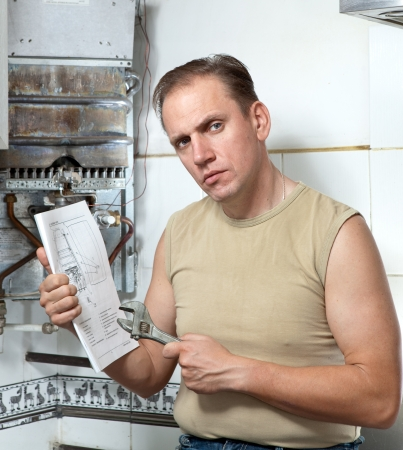 The man with a wrench looks the instruction on repair a gas water heater.   photo