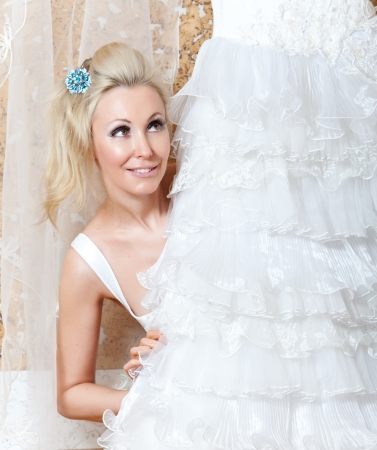 ruching: The young woman near to a wedding dress dreams about wedding
