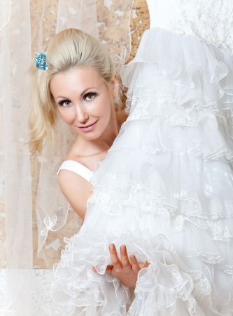 The young woman near to a wedding dress dreams about wedding