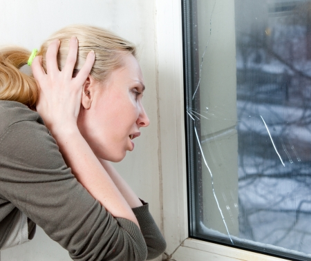 snow break: The sad young woman near a window with the burst, broken glass   Stock Photo