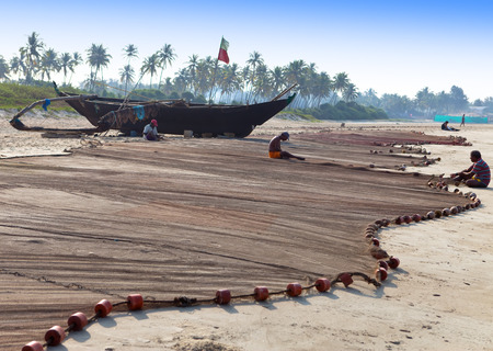 india fisherman: GOA, INDIA - FEBRUARY 01  fisherman repairs fish nets after morning fishing on February 01, 2014 in Goa, India Editorial