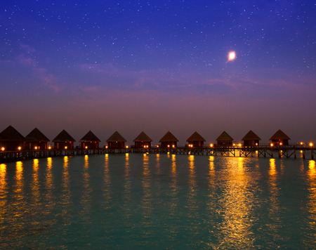 fool moon: houses on piles on water at night in  fool moon light