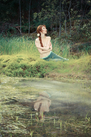 adult mermaid: The girl sits on the bank of wood lake,with a retro effect