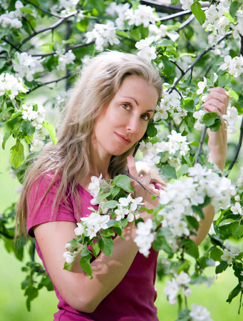 young attractive woman standing near the blossoming apple tree. Stock Photo - 27646172