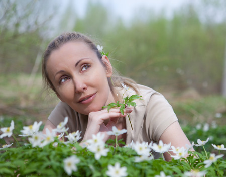 The young beautiful woman on a glade of blossoming snowdrops in the early spring Stock Photo - 27646174