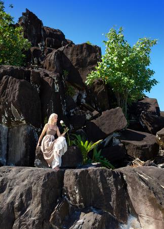 borabora: The woman in a long dress on black stones. Polynesia.