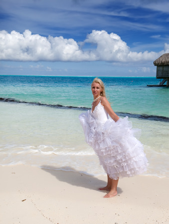 borabora: The young beautiful woman in a bride dress standing at sea edge   Stock Photo