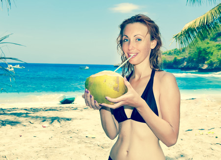 Beautiful girl with coconut on background of sea,with a retro effect photo
