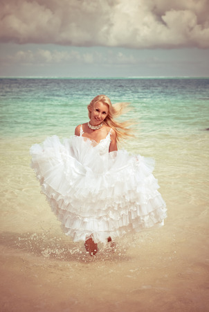 borabora: The young beautiful woman in a dress of the bride runs on waves of the sea,with a retro effect
