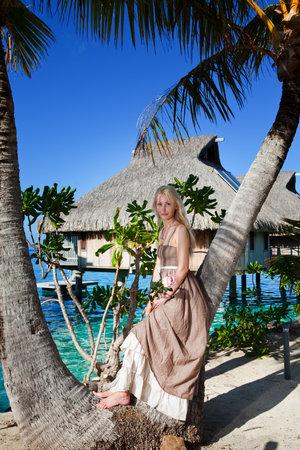 borabora: The beautiful woman in a long dress on the palm tree near the sea.