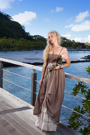 borabora: The beautiful woman in a long dress sits on the wooden bridge on the tropical island