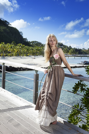 borabora: The beautiful woman in a long dress on the wooden bridge near the sea.