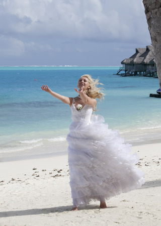 borabora: The young beautiful woman in a dress of the bride  at edge of the sea
