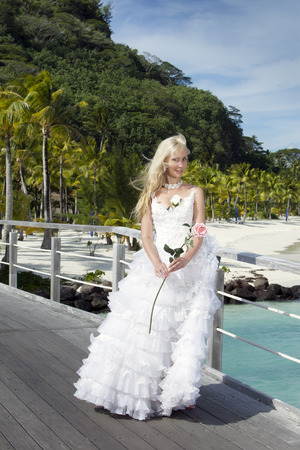 borabora: The beautiful woman in a long dress of the bride on the wooden bridge on the tropical island Stock Photo