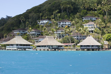 lodges: Hill slope by the sea and lodges on a slope. Polynesia. Editorial