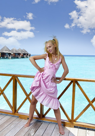 sundress: Young beautiful girl stands in pink sundress on sundeck of villa on water, Maldives