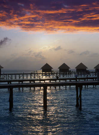 lodges: Silhouette of lodges in the sea at sunset. Maldives