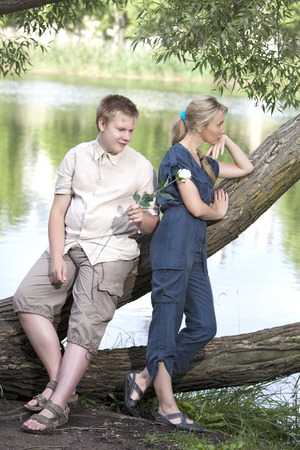 reconciliation: Young guy and girl on the nature near lake, reconciliation after quarrel Stock Photo