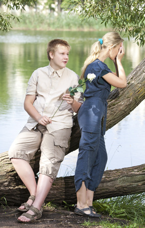 Young guy and girl on the nature near lake, reconciliation after quarrel photo
